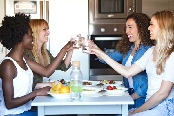 Four women toast with glasses of water over a healthy meal.